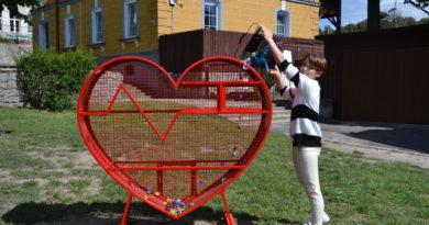 Zdjęcie kobiety wsypującej nakrętki do kosza w kształcie serca